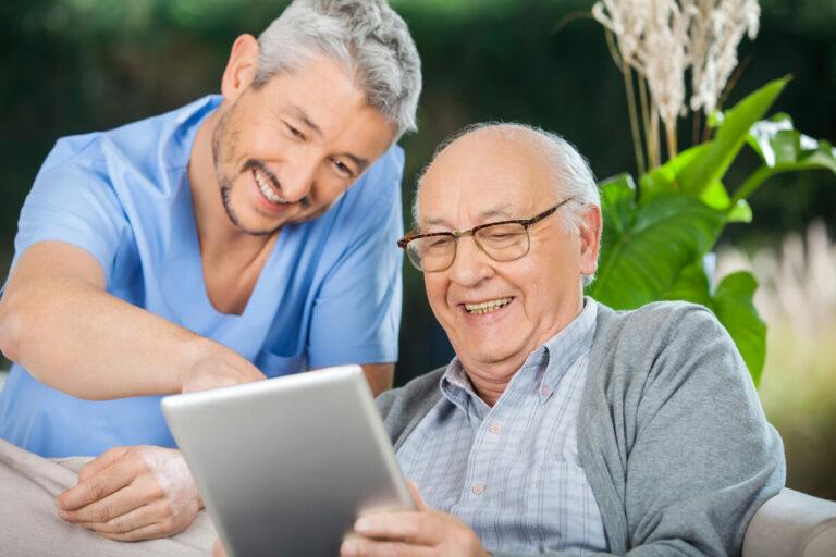 SoCo Village | Senior and caregiver looking at a tablet