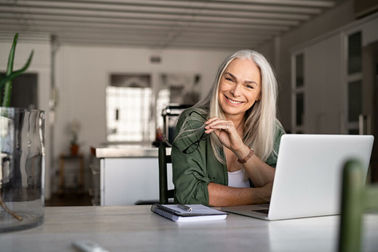 SoCo Village | Senior smiling while on her computer