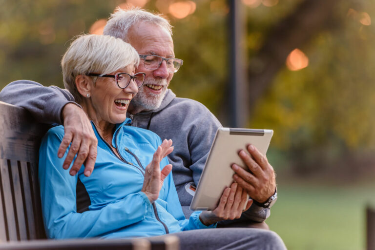 SoCo Village | Senior couple sitting on a bench on their tablet